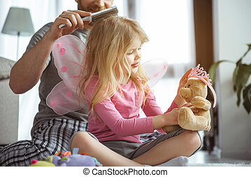 Pretty girl playing with toys near her daddy