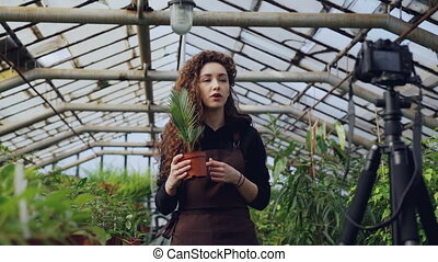 Pretty girl popular blogger is recording video about plants...