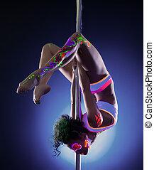 Pretty girl posing hanging upside down on pylon
