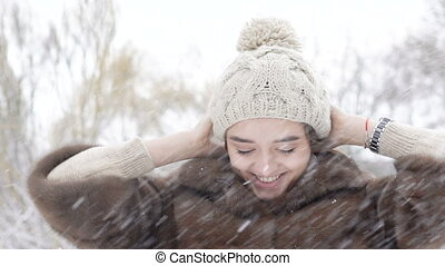 Pretty girl posing, touching her hair and winter hat in snowy day. Slowly