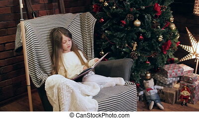 girl reading a book near a Christmas tree