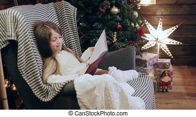 pretty girl reading a book near a Christmas tree