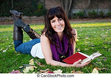 pretty girl reading book in grass