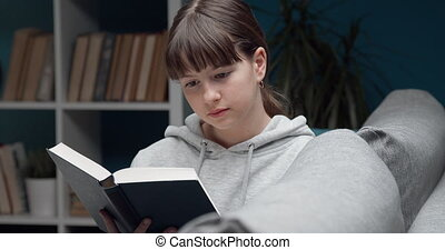 Pretty young girl with brown hair sitting on grey couch and reading interesting book at home. Teenager in casual clothing using her time profitably.