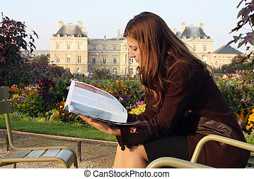 Pretty girl reading magazine in Luxembourg garden (Paris). Late afternoon sun. Autumn colors.