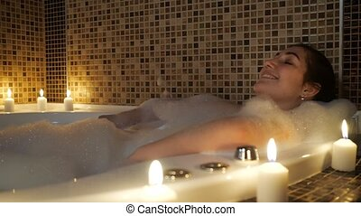 pretty girl relaxes in bubble bath by candlelight at night
