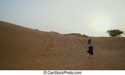 Pretty girl runs in the desert. Beautiful woman is running at sunset. Slow motion