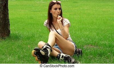 pretty girl sits in rollers on the lawn and sucks lollipop