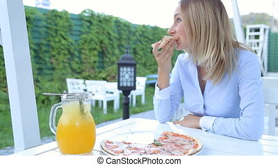 Pretty girl sitting in the restaurant and eating pizza