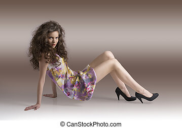 pretty girl sitting on a floor with body in profile
