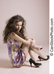 pretty girl sitting on a floor with knees in the arms