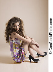 pretty girl sitting on a floor with sensual expression