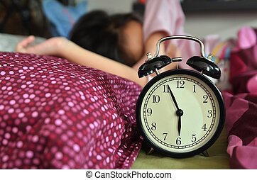 Pretty girl sleeping on the background of a retro alarm clock