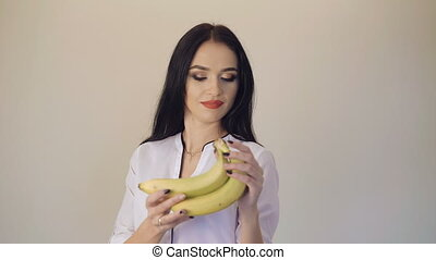 Pretty girl smiling and posing with two bananas on camera in 4K
