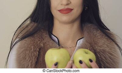 Pretty girl smiling and posing with two big green apples on background. Slowly