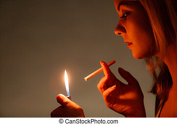 Pretty girl smoking cigarette using lighter. Addicted...