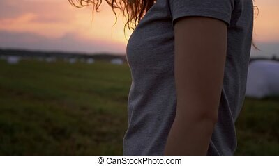 Pretty girl standing at sunset on the field