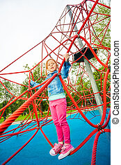 Pretty girl standing on red net of playground