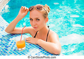 Pretty girl swimming in a pool with juice and glasses
