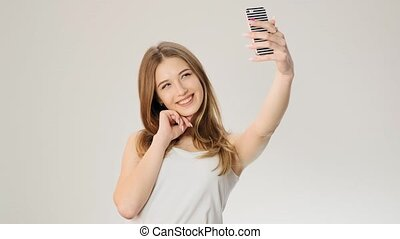 Pretty girl taking selfie with phone at studio slow motion