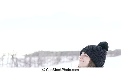 Pretty girl throwing up snow and smiling in winter day. Slowly