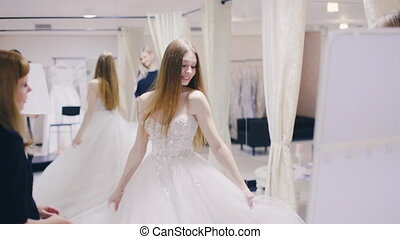 pretty girl trying on wedding gown and spinning - woman...