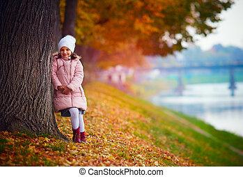 pretty girl walking in autumn park among fallen leaves