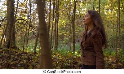 Pretty girl walking through autumn woods holding a picnic...