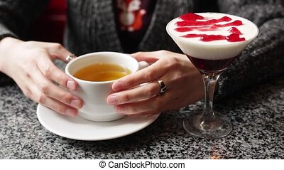 Pretty girl warms her hands, holding a cup of hot black or green tea.