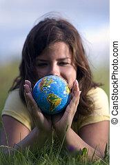 Pretty girl watching earth globe - Pretty teen girl watching...
