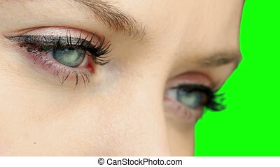 Pretty girl wearing eyeliner looking and blinking on green...