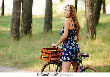 Pretty girl with a bicycle in the forest.