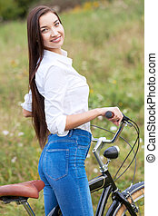 Pretty girl with a bicycle posing outdoors