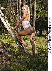 Pretty girl with bare butt near a haystack.