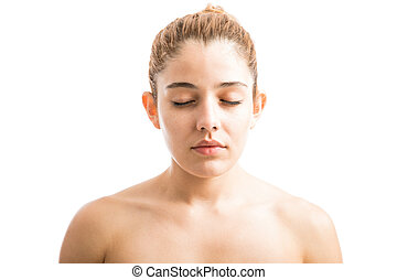 Attractive young Caucasian woman with bare shoulders and her eyes closed in a studio