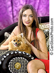 pretty girl on a black expensive sofa with doggie