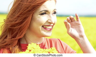 Pretty girl with golden hair with bouquet of rape blossom in the field. Slowly