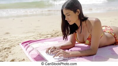 Pretty girl with laptop on tropical beach