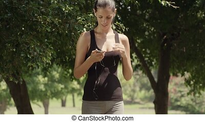 Pretty girl with mp3 player jogging - Sport and music,...