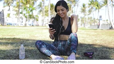 Pretty girl with phone on workout in park