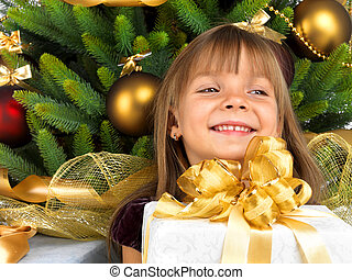 Pretty girl with present near the Cristmas tree