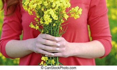 Pretty girl with rape bouquet on field backgrount. Slow motion