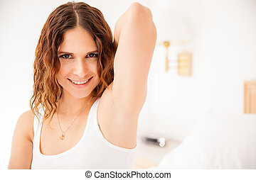 Closeup of a beautiful young Hispanic woman raising her arm and showing her smooth armpits