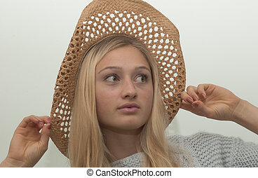 Pretty Girl with the Straw Hat - A girl with blond hair is...