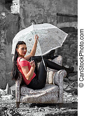 Pretty girl with umbrella sitting in chair