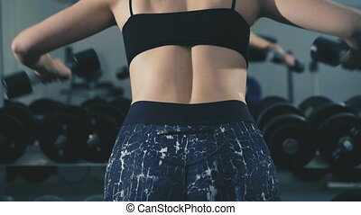 Pretty girl working out in the gym using dumb-bells for muscles and back in 4K