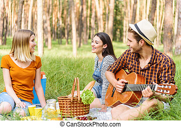 Pretty girls and guy relaxing in nature
