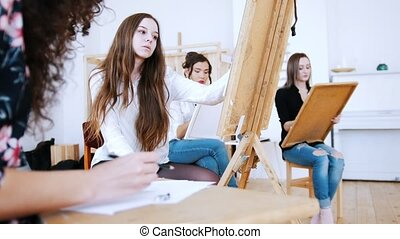 Pretty girls are sitting behind the easel and drawing