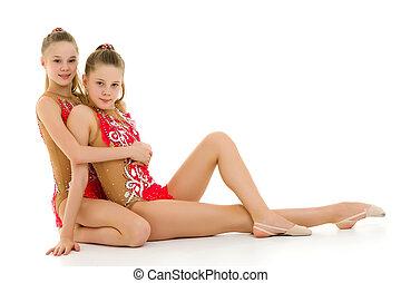 Pretty Girls Gymnasts Performing Rhythmic Gymnastics Exercise.