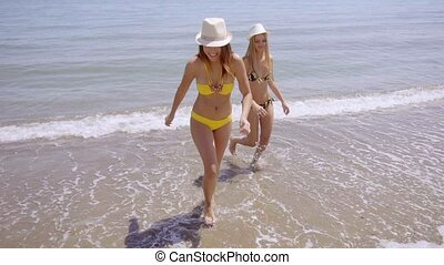 Pretty girls in bikinis paddling in the sea